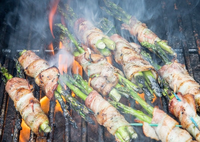 bacon wrapped asparagus cooking over charcoal grill