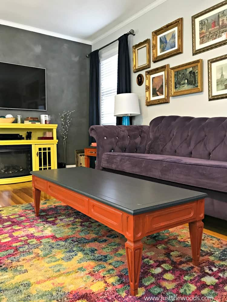 gray wall in living room, orange painted tables, yellow media console, purple sofa, repainted furniture