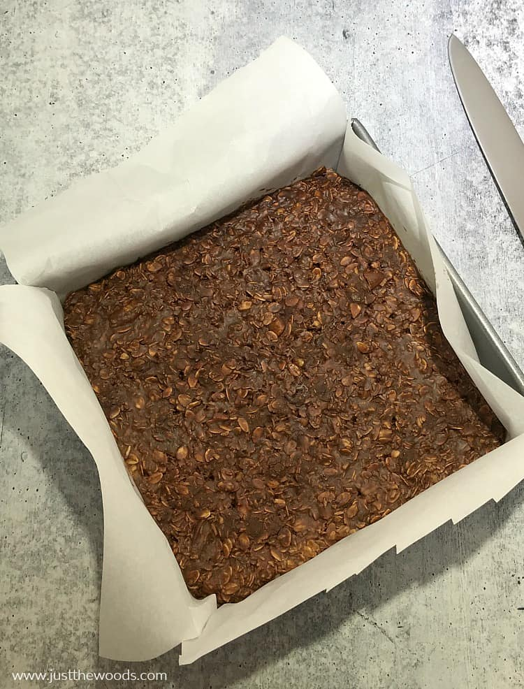 chocolate oat bar recipe in parchment paper lined pan after hardening in refrigerator