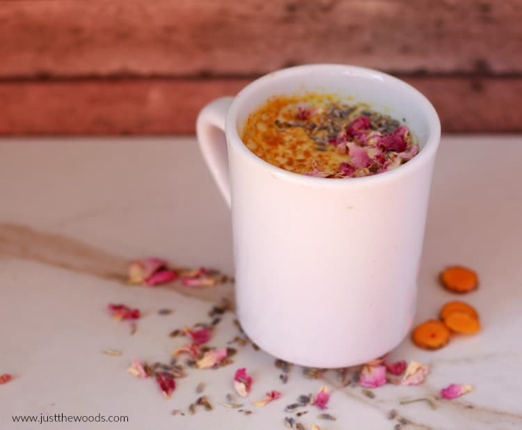 golden milk in white mug with pink flowers and turmeric