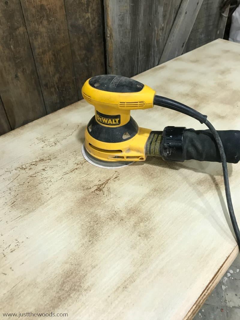 yellow dewlap sander on wood dresser