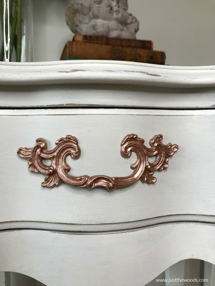 white distressed painted furniture with metallic paint hardware
