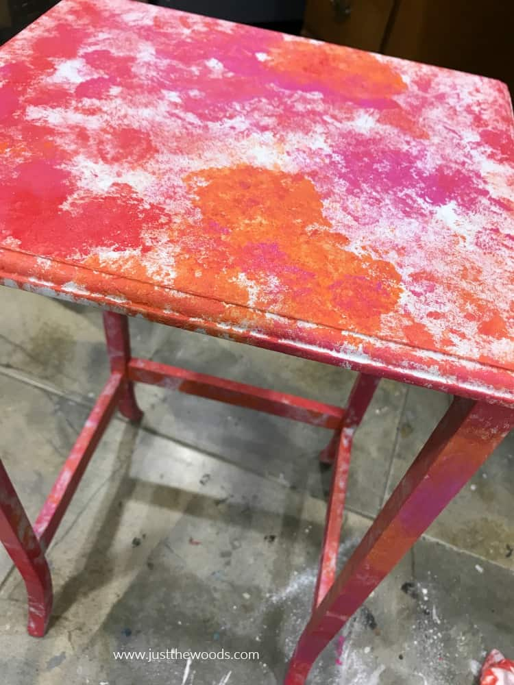 table painted with random splotches of red pink and orange paint