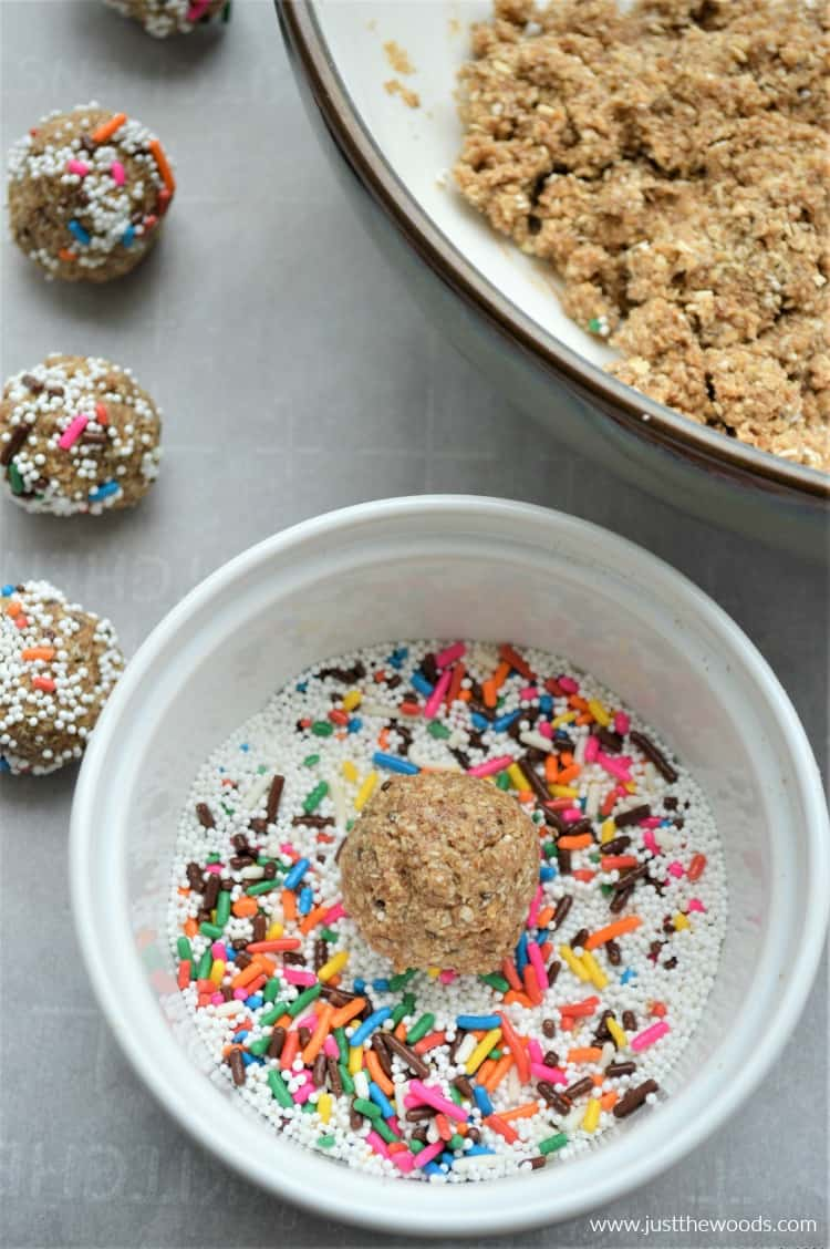 cookie dough ball in bowl of rainbow sprinkles