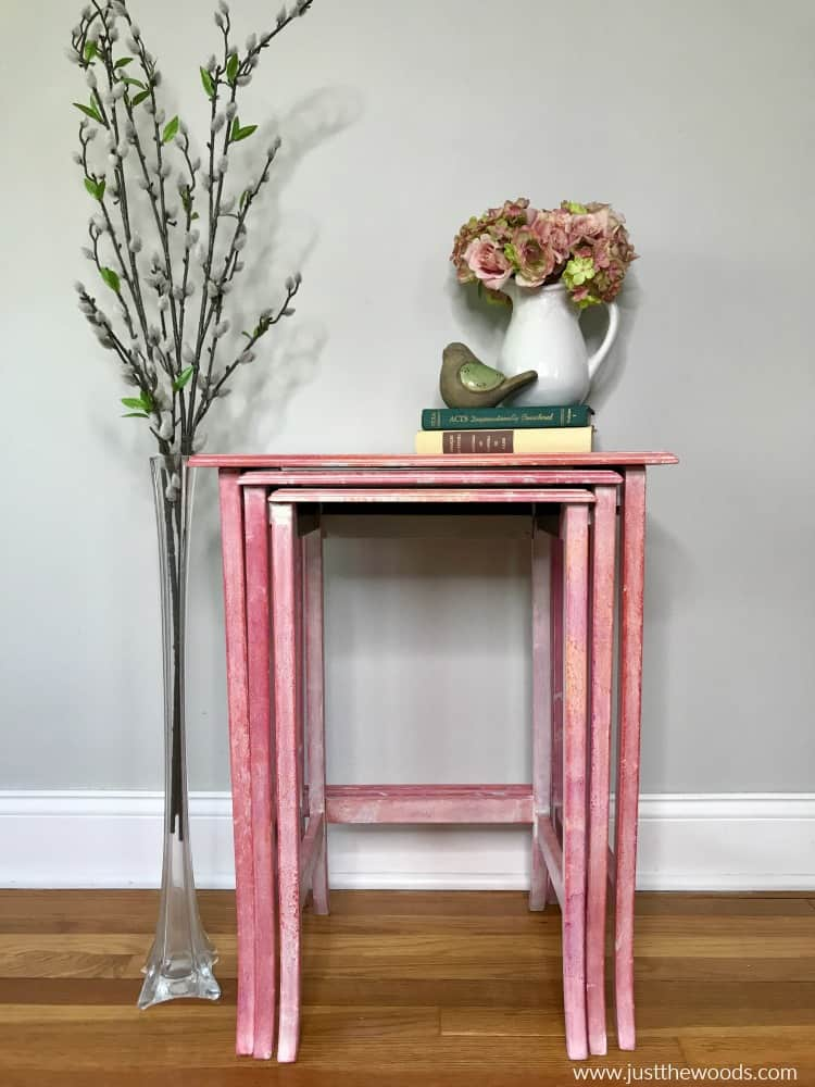 pink nest of tables, tables with two books and floral vase